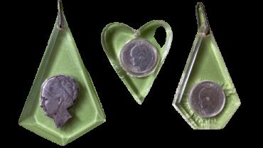 Een verzameling van drie Wilhelmina munten in vliegtuigglas